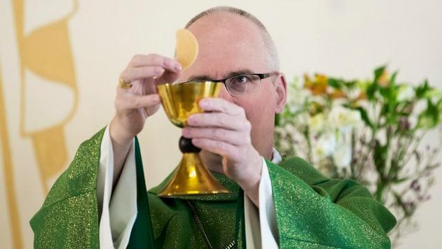 Der Bischof hält den Kelch hoch während einer Messe.