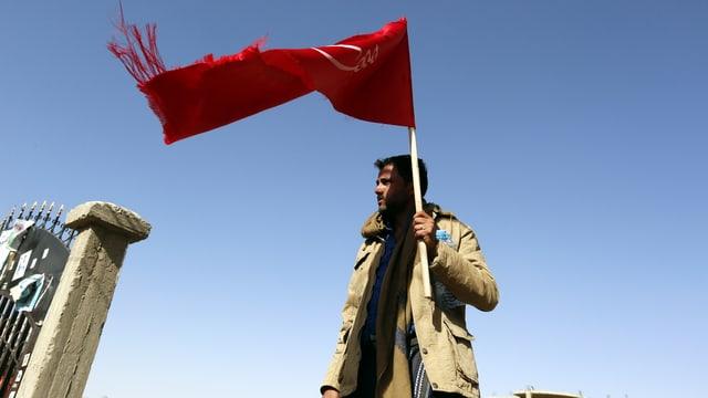 Ein Houthirebell mit einer roten Fahne