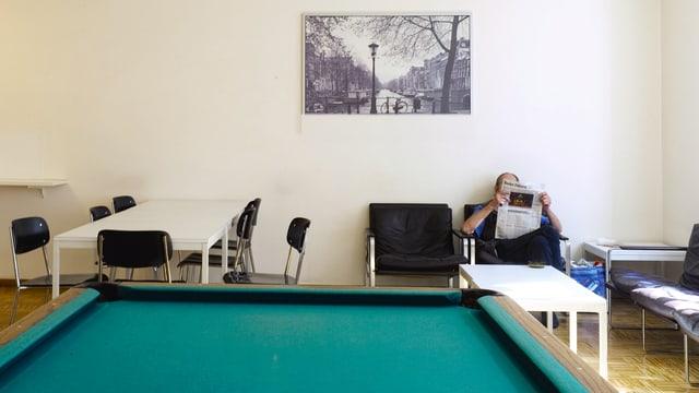 Ein Mann liest in einem Lesesessel eine Zeitung, vor ihm ein Billardtisch