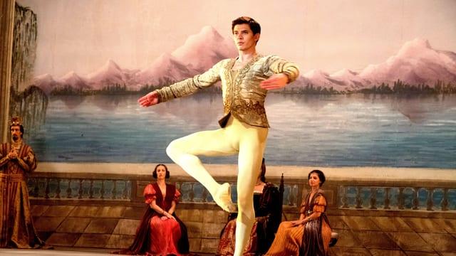 Ein Balletttänzer Tanzt auf einer Bühne in der Pirouetten-Position.