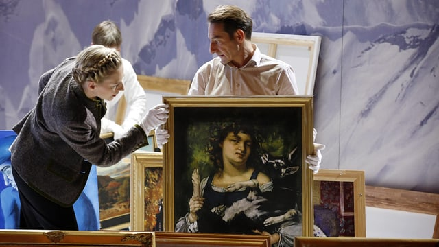 Drei Personen sehen sich Gemälde an.