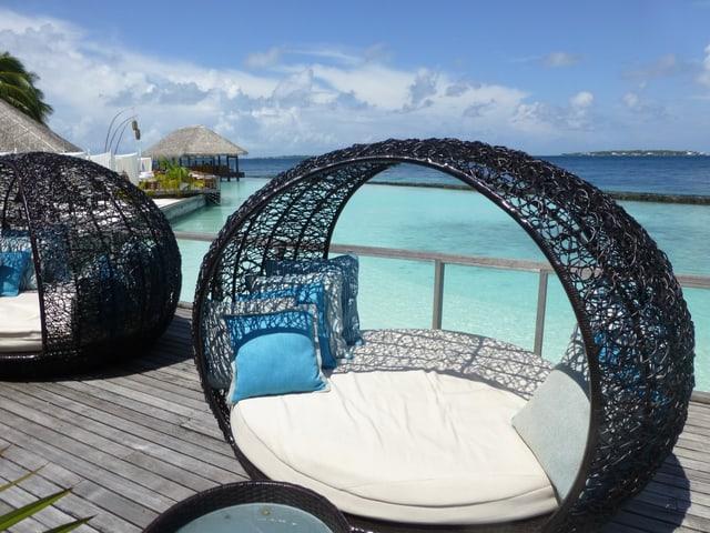 Lounge auf einem Holzsteg, dahinter das Meer.