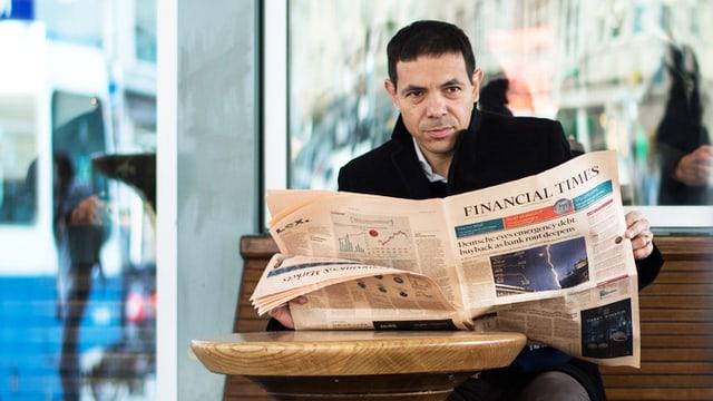 Mann sitzt im Strassencafe und liest Zeitung.