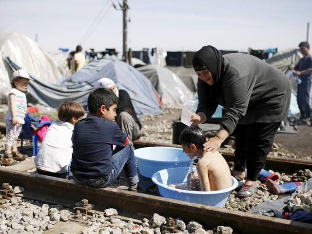 Eine Frau wäscht ein Kind, das in einer Plastikschale sitzt auf einer Schiene in Idomeni. Darum herum versammelt sind weitere Kinder. (reuters)
