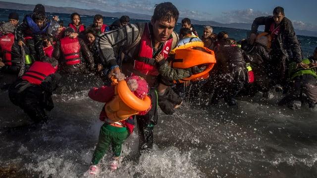 Ein Mann rettet zwei Kinder aus dem Wasser.