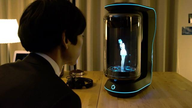 Ein junger Mann im Anzug sitzt am Tisch uns spricht zu einem Hologramm hinter der Glasscheibe.