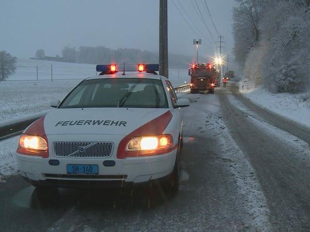 Polizei- und Feuerwehrautos räumen einen Umfall von der verschneiten Strasse.