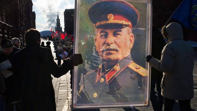 Zwei Personen tragen ein meterhohes Bild von Stalin durch die Moskauer Innenstadt.