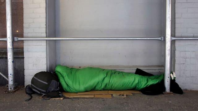 Person schläft in einem Schlafsack auf dem Boden.