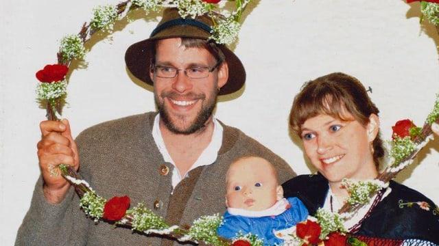 Familie Willmann in bayrischer Tracht mit Kranz aus Tannenzweigen und roten Rosen