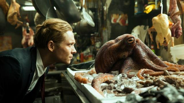 Matthias Schweighöfer beugt sich zu einem, in einem Restaurant aufgebahrten Tintenfisch herunter und schaut ihm in die Augen.