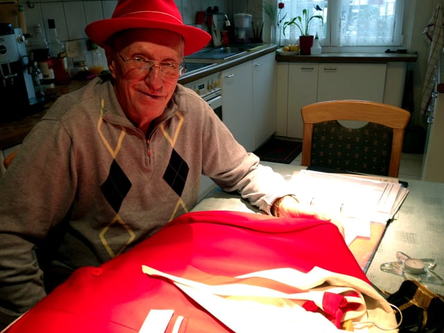 Eduard Roth sitzt am Tisch, vor ihm das rote Hans-Roth-Ehrenkleid.
