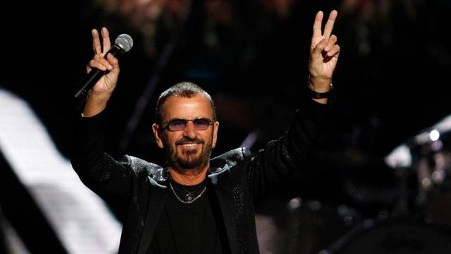 Ein Mann mit Mikrofon in der Hand macht mit beiden Händen das Peace-Zeichen.