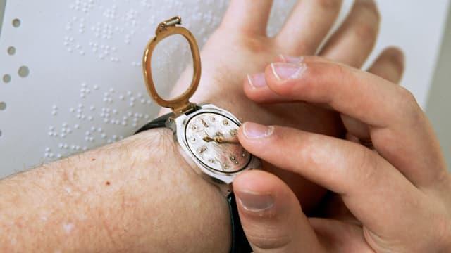 Zwei Hände liegen auf einem Blatt mit Blindenschrift, die eine Hand ertastet auf einer Armbanduhr mit aufgeklapptem Deckel die Zeit.
