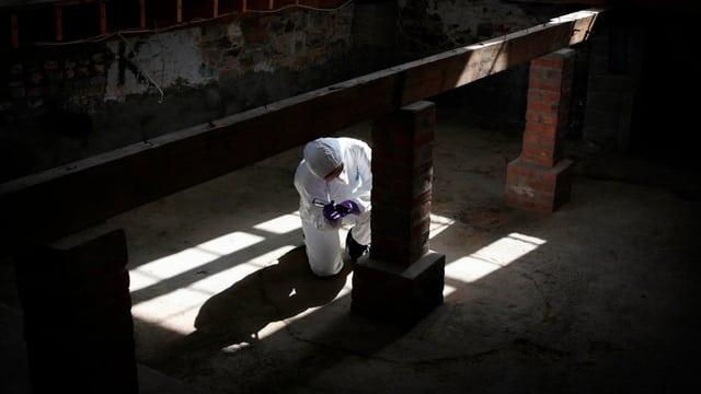 Ein Forensiker bei der Spurensicherung in einem dunklen Keller.