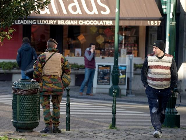 Belgischer Soldat mit dem Rücken zur Kamera beobachtet einen Schokoladeladen, ein entgegenkommender Passant mustert ihn