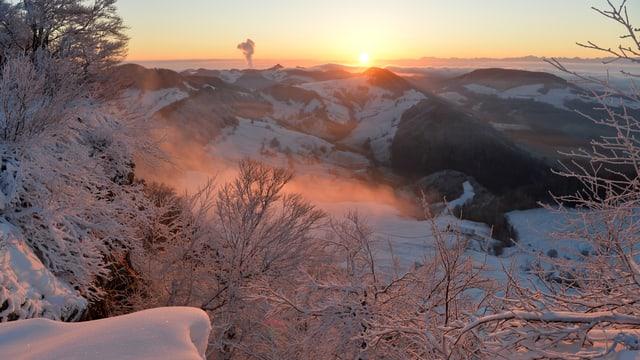 Sonnenaufgang b ei klarem Himmel über dem veschneiten Jura.