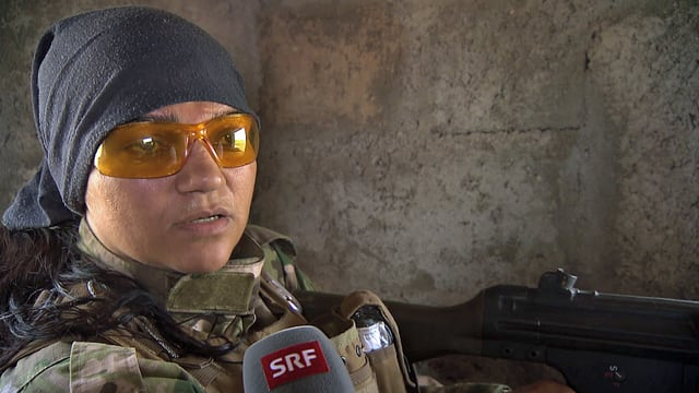 Eine Frau mit Kopftuch und Sonnenbrille mit einem Gewehr im Gespräch mit SRF.