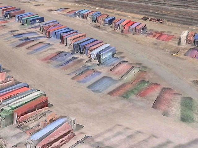 3D-Kartenansicht: Stark verbogene, farbige Schiffscontainer auf grauem Boden