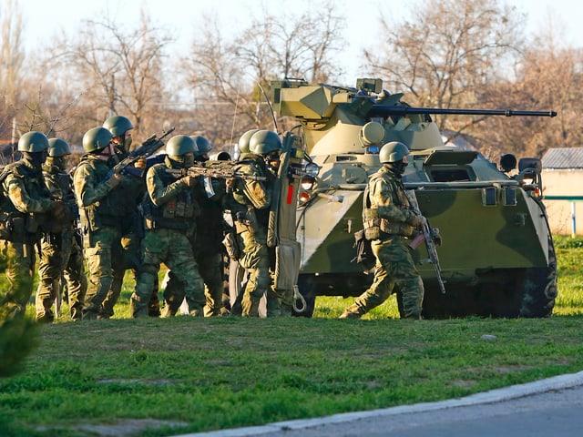 Schwerbewaffnete Soldaten neben Panzerfahrzeug.