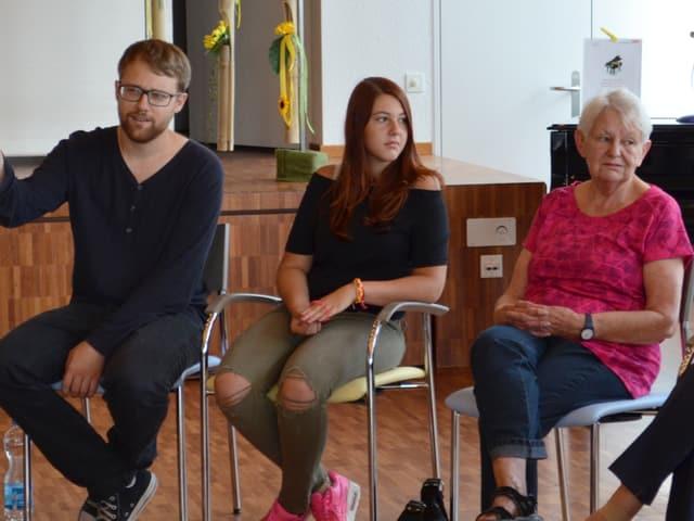 Ein Mann mit Brille sitzt neben einer jungen Frau und einer älteren Dame.