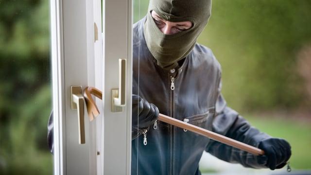 Ein Einbrecher bricht ein Fenster auf