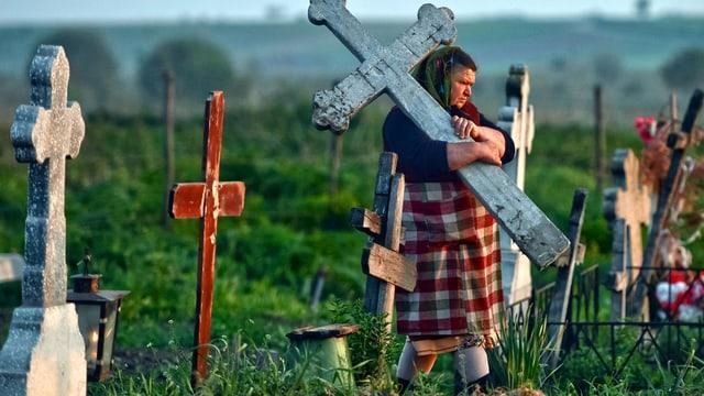 Eien Frau auf einem ländlichen Friedhof trägt einen steinernen Grabstein in Kreuzform.