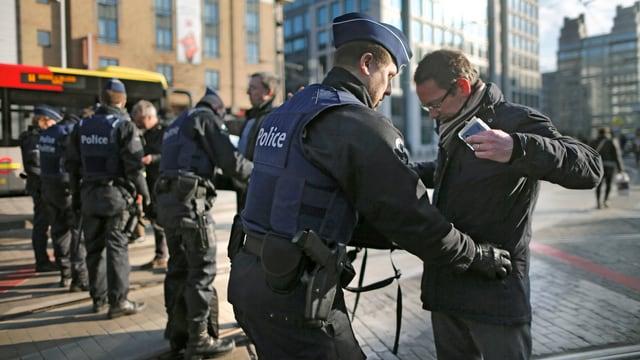 Mehrere Polizisten durchsuchen in Brüssel Passanten.