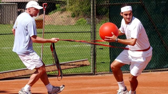 Paganini macht mit Federer eine Sprint-Übung mit Ball und Gummizug.