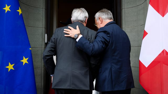 Jean-Claude Juncker und Johann Schneider-Ammann treten durch einen Eingang.