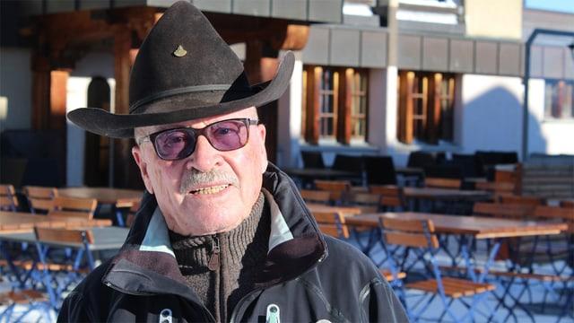Ein Mann mit Hut und Brille auf der Terrasse eines Restaurant.