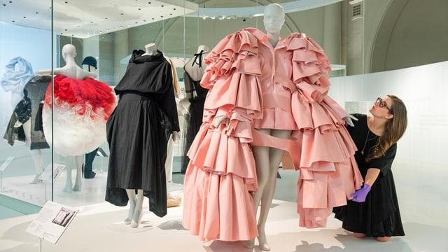 Eine Frau macht sich in einem Museum an einer Kleiderpuppe zu schaffen.