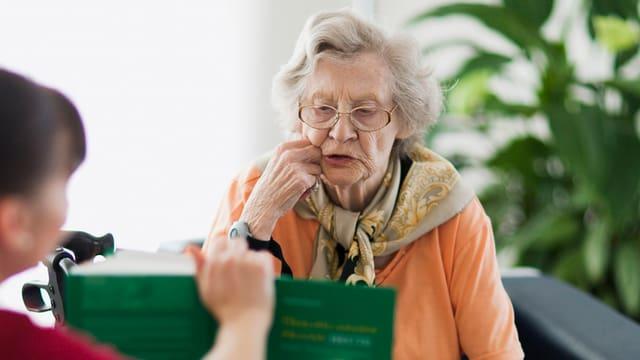 Eine Frau liest einer älteren Dame aus einem Buch vor.