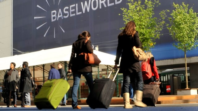 Zwei Frauen vor dem Logo der Baselworld.