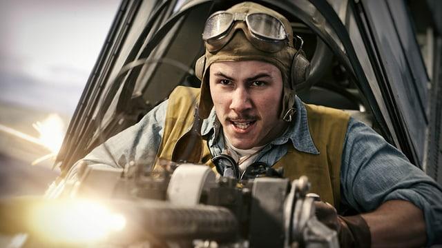 Ein Militärpilot ballert mit seinem Maschinengewehr lächelnd in Richtung Kamera.