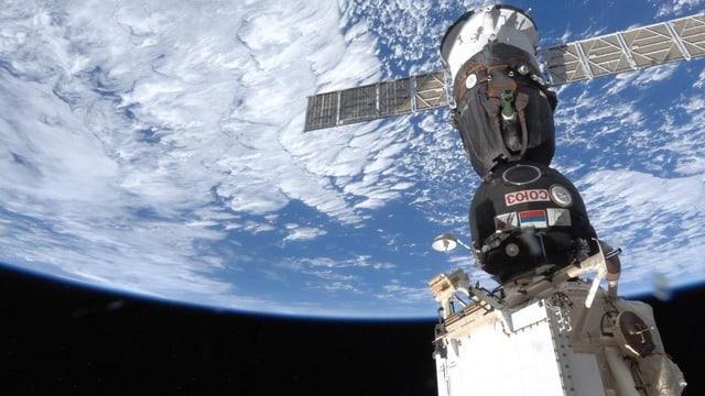 ISS und Sojus-Raumtransporter im All fotografiert mit Sicht auf die Erde.