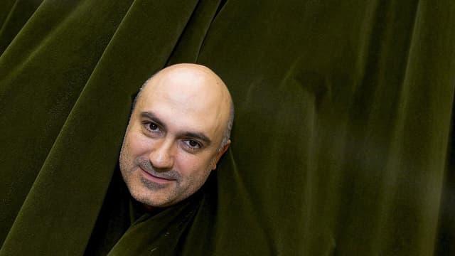 Der Regisseur Calixto Bieito steckt seinen Kopf durch einen grünen Theatervorhang.