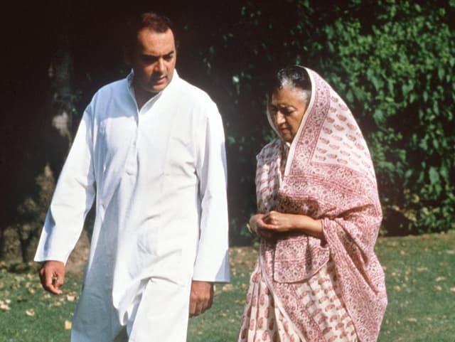 Rajiv und Indira Gandhi in einem Park gehend.