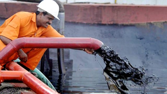 Arbeiter an einer Leitung aus der Öl fliesst.