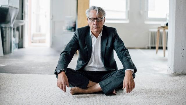 Ein Mann im Anzug meditiert.