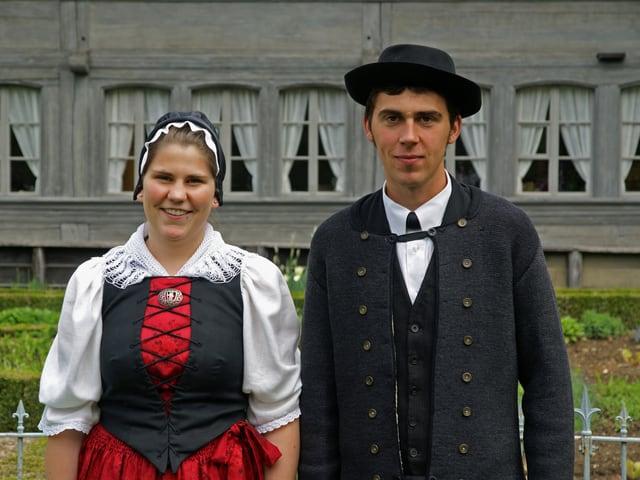 Trachtenpaar vor Bauernhaus.