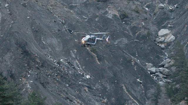 Helikopter fliegt vor gebirgigem Gelände.