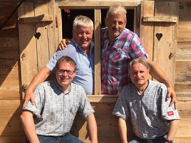 Die Schwingerkönige stehen im Fenster eines Holzchalets, davor auf einem Bank die Moderatoren.