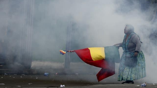Eine Frau mit bolivianischer Flagge im Tränengas-Nebel