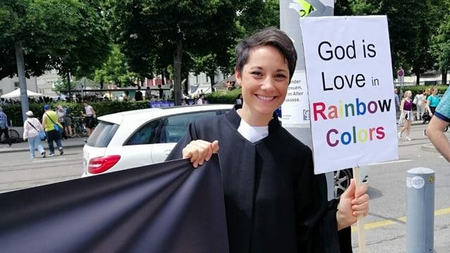 """Priscilla Schwendimann mit einem Banner. Darauf steht """"God is Love in Rainbow Colors"""""""
