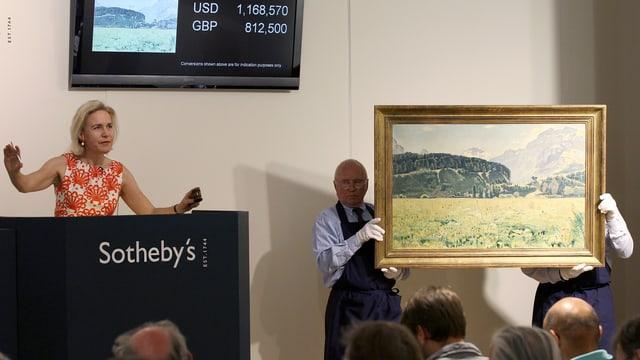 Eine Auktion, bei der zwei Herren ein Gemälde präsentieren.