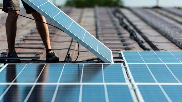 Jemand legt eine Photovoltaïk-Platte auf ein Dach zwecks Installation.