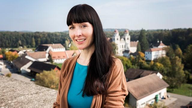Frau mit langen schwarzen Haaren steht lächelnd vor einer Mauer.
