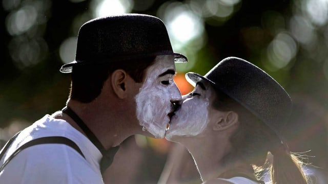 Zu sehen sind zwei als Mimen verkleidete Personen, ein Mann und eine Frau, die sich küssen.
