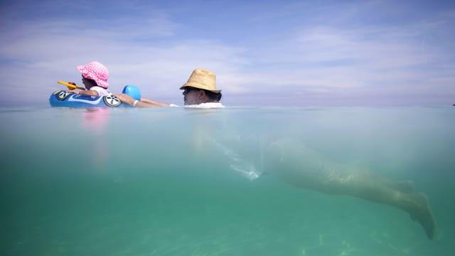 Mann und Kind beim Schwimmen im Meer